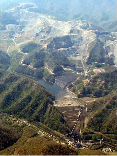 Blasted mountains (top); mandmade lake (impoundment) holding 2.8 billion gallons of toxic sludge (center), containment wall and conveyor belts leading down to Massey's Goals Coal processing plant (bottom center), Massey coal silo and Marsh Fork Elementary School (bottom right), April 29, 2009/Vivian Stockman, flickr.com