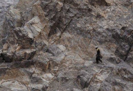Man walking in rocky terrain, Afghanistan, Oct 5, 2011/ Tauseef Mustafa, AFP Google