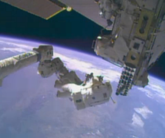 NASA astronaut Mike Hopkins attaching himself to ISS robotic arm with Earth in background, Dec 24, 2013/NASA TV, Space.com