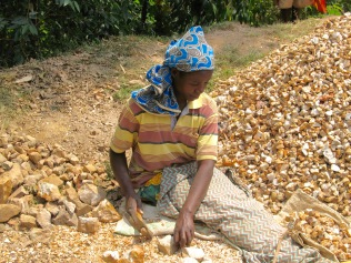 Woman breaking rocks for gravel, road to Bwindi