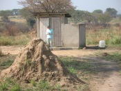 Gini exiting outhouse, termite mound in foreground, Queen Elizabeth National Park