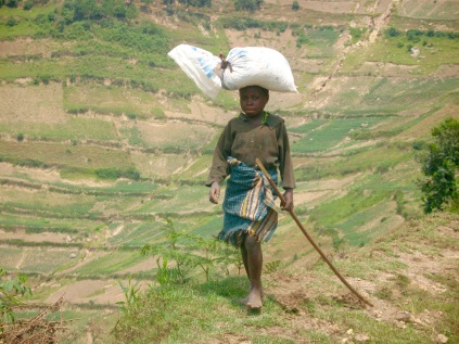 Girl who had just come up a steep slope with sack on head, road to Bwindi