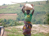 Girl along road with sack on head, road to Bwindi