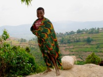 Another girl who just came up a steep slope carrying heavy sack of potatoes, road to Bwindi