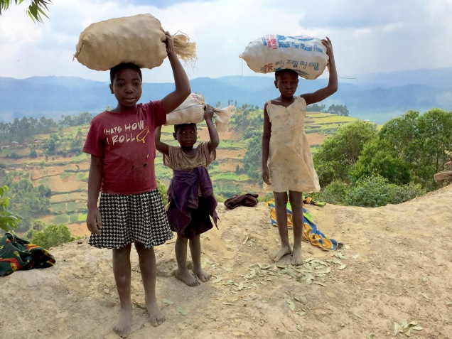 Three girls who've just climbed a steep slope with sacks, road to Bwindi
