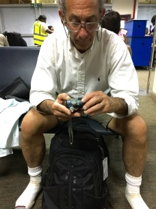 Marc checking his camera in waiting area prior to departure, Entebbe Airport