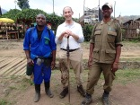 Marc returns to car park with porter and guide after arduous, successful Karisoke climb, Bisate