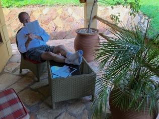 Marc reading on patio, Le Petit Village, Kampala