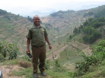 Kenneth standing on road above his home valley, road to Bwindi