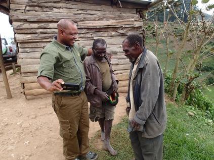 Kenneth warmly embraces two Batwa men during vista stop, road to Lake Bunyonyi
