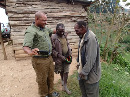 Kenneth warmly embraces two Batwa men during vista stop, road to Lake Bunyonyi