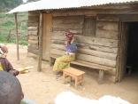 Woman outside cabin waving off Marc's camera, vista stop, road to Lake Bunyonyi