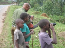 Kenneth helps boys figure out how to look through Gini and Marc's binoculars, road to Lake Bunyonyi