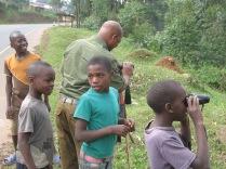 Boys waiting their turn for first look through binoculars, road to Lake Bunyonyi