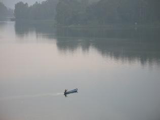 Man in canoe, returning from market on shore of Lake Bunyonyi