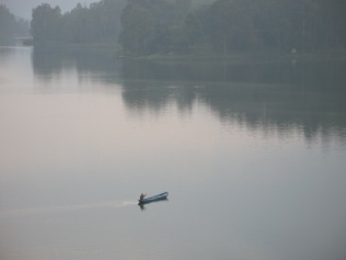Man in canoe, returning from market on shore of Lake Bunyonyi