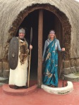 Trekking friends Darren and Lauren from Cayman Islands were pressed into donning royal garb, standing at entrance to an accurate replica of traditional king's palace, Iby'Iwacu Cultural Village, Kinigi