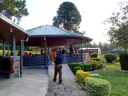 Kenneth approaching pavilion where trekkers gather, chat and have coffee while waiting to be assigned to their groups, Volcanoes National Park Headquarters, Kinigi